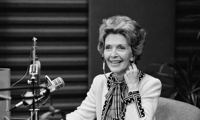 First lady Nancy Reagan smiles as she adjusts her headphones during a guest spot on a radio talk show, Oct.7, 1982 in Los Angeles.  Mrs. Reagan spent most of the 45-minute stint on KABC's show discussing and answering telephone callers' questions about the Foster Grandparents program. (AP Photo/Wally Fong)