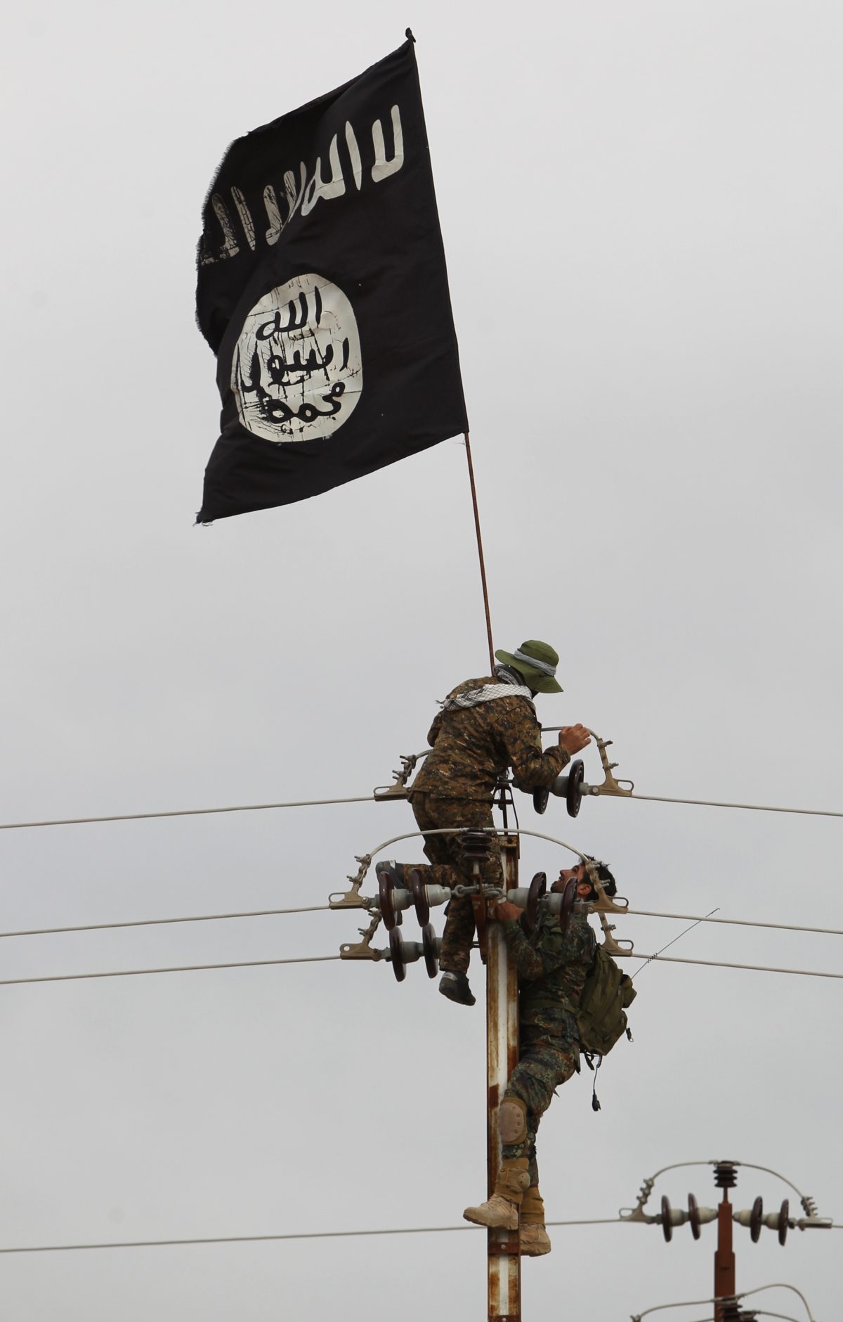 Iraqi Shiite fighters from the Popular Mobilization units take off an Islamic State flag from an electricity pole on March 3, 2016, during an operation in the desert of Samarra aimed at retaking areas from ISIS jihadists. (Ahmad al-Rubaye/AFP/Getty Images)