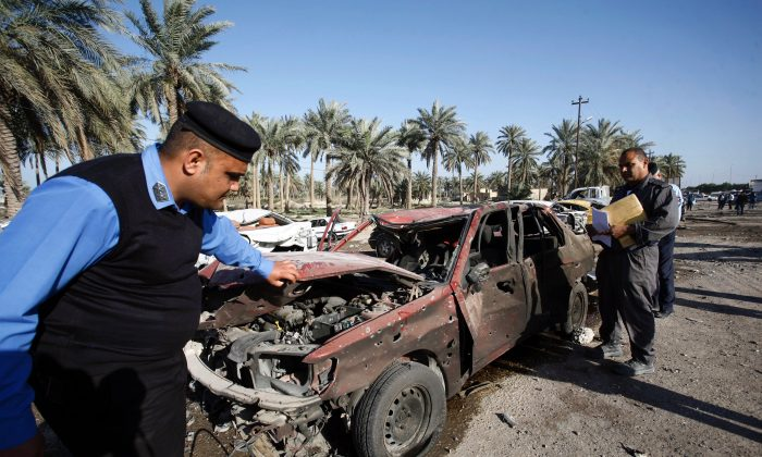Iraqi emergency responders inspect debris at the site of a truck bomb, that exploded at a crowded checkpoint, in the Iraqi city of Hilla, south of Baghdad on March 6, 2016. The Islamic State jihadist group claimed responsibility for a suicide truck bomb blast that killed at least 47 people in the city of Hilla. (Haidar Hamdani/AFP/Getty Images)
