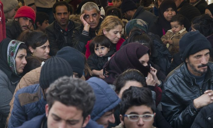 Migrants wait near the border gate at the northern Greek border station of Idomeni on March 6, 2016. Greek police officials saidy Macedonian authorities have imposed further restrictions on refugees trying to cross the border, saying only those from cities they consider to be at war can enter. (AP Photo/Vadim Ghirda)