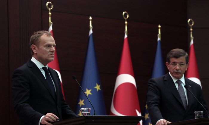 """Turkey's Prime Minister Ahmet Davutoglu (R) and European Council President Donald Tusk at a joint press conference in Ankara, Turkey, on March 3, 2016. Tusk says it is up to Turkey to decide what further measures it can take to reduce the flow of migrants but says many in Europe favor a mechanism that would allow the """"fast and large-scale"""" shipment of migrants back to Turkey and such a mechanism would """"effectively break the business model of the smugglers. (AP Photo/Burhan Ozbilici)"""