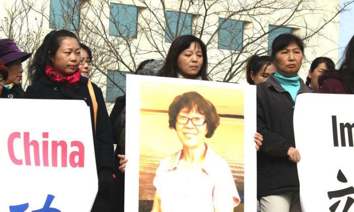 Karen Xu on March 3, 2016, holds a poster of her mother, Wang Sirong, who is currently being held at a detention center in Tianjin. (Minghui.org)