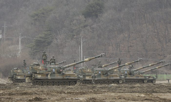 "South Korean army soldiers stand on their K-55 self-propelled howitzers during an annual exercise in Paju, near the border with North Korea, Monday, March 7, 2016. North Korea on Monday issued its latest belligerent threat, warning of an indiscriminate ""pre-emptive nuclear strike of justice"" on Washington and Seoul, this time in reaction to the start of huge U.S.-South Korean military drills. (AP Photo/Ahn Young-joon)"