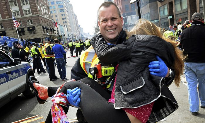 In this April 15, 2013 file photo, Boston Firefighter James Plourde carries Victoria McGrath from the scene after a bombing near the Boston Marathon finish line. A Northeastern University spokesman said Monday, March 7, 2016, that McGrath, originally from Westport, Conn., and another student were killed in a car accident in Dubai over the weekend while on a personal trip. (AP Photo/MetroWest Daily News, Ken McGagh, File) MANDATORY CREDIT: METROWEST DAILY NEWS, KEN MCGAGH