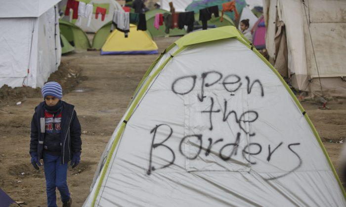 Migrant child walks past a tent at the northern Greek border station of Idomeni on March 7, 2016. (AP Photo/Visar Kryeziu)