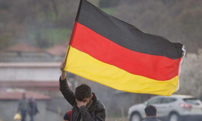 A migrant wipes his eyes holding a German flag at the northern Greek border station of Idomeni on March 6, 2016. (AP Photo/Vadim Ghirda)
