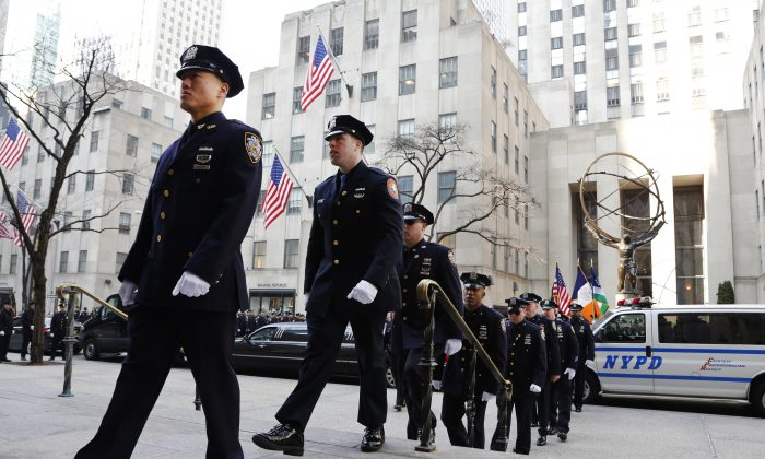 Members of the New York Police Department arrive for the funeral for Euless, Texas police officer David Hofer, Monday, March 7, 2016, at St. Patrick's Cathedral in New York. Hofer was killed Tuesday, March 1 while responding to reports of shots fired in a park. Hofer was a 2008 graduate of New York University who served in the NYPD for five years before joining the  Euless Police Department in 2014. (AP Photo/Mark Lennihan)