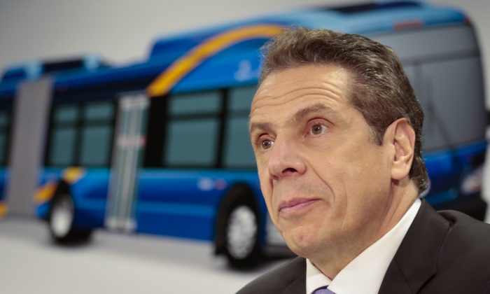 Gov. Andrew Cuomo listens during a news conference announcement that new buses, like that shown in a background display, will be introduced in Queens starting early April equipped with wifi and rechargeable ports, Tuesday, March 8, 2016, in New York. (AP Photo/Bebeto Matthews)