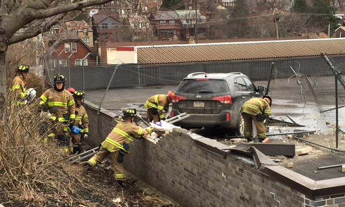 Emergency personnel check a vehicle that crashed onto the roof of a supermarket, Tuesday, March 8, 2016, in Pittsburgh. The crash happened late Tuesday morning at a Giant Eagle store in the city's Greenfield neighborhood. (Darrell Sapp/Pittsburgh Post-Gazette via AP)