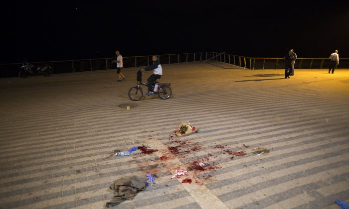 People walk by blood stains at the scene of a stabbing attack in Jaffa, a mixed Jewish-Arab part of Tel Aviv, Israel, Tuesday, March 8, 2016. (AP Photo/Oded Balilty)