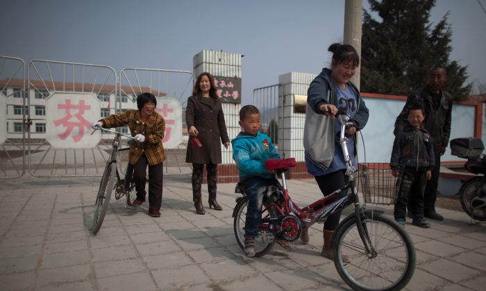 Parents and children leave a school in Chengde, Hebei Province on March 21, 2013. Middle-aged women are getting pregnant again after China loosened its one-child policy. (Ed Jones/AFP/Getty Images)