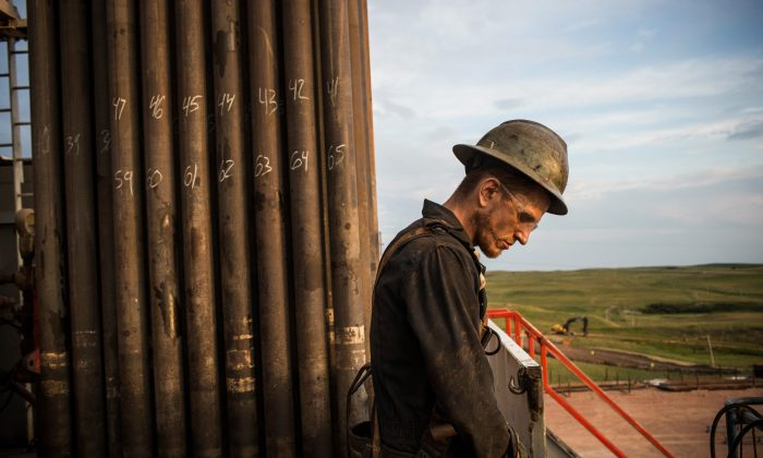 Ray Gerish, a floor hand for Raven Drilling, works on an oil rig drilling into the Bakken shale formation outside Watford City, N.D., on July 28, 2013. North Dakota has been experiencing an oil boom in recent years, due in part to new drilling techniques including hydraulic fracturing and horizontal drilling. In April 2013, USGS released a new study estimating the Bakken formation and surrounding oil fields could yield up to 7.4 billion barrels of oil, doubling their estimate of 2008, which was stated at 3.65 billion barrels of oil. Workers for Raven Drilling work twelve hour days fourteen days straight, staying at a camp nearby, followed by fourteen days off. (Andrew Burton/Getty Images)