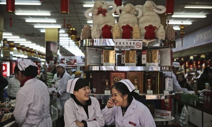 Chinese clerks chat as they wait for customers at a market in Beijing on Jan. 19, 2016.  (Kevin Frayer/Getty Images)