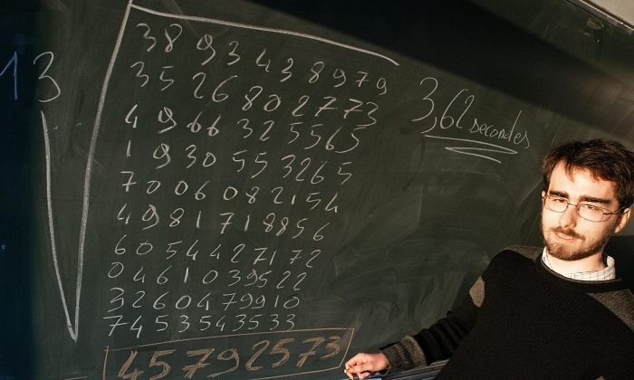 Alexis Lemaire, 24, posing in front of a blackboard in Reims, France, 20 December 2004 after he set a new world record as he became the first person to figure out the 13th root of a 200-digit number by mental arithmetic alone. (FRANCOIS NASCIMBENI/AFP/Getty Images)