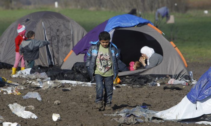 A boy walks through mud in an improvised camp on the border line between Macedonia and Serbia near northern Macedonian village of Tabanovce, on March 8, 2016. (AP Photo/Boris Grdanoski)