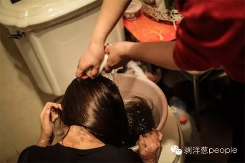 Zhou Yan washing her hair with the help of her mother. (via Beijing News)