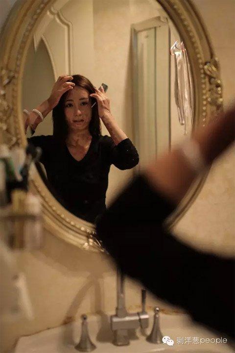 An adult Zhou Yan looks herself in the mirror (via  Beijing News)