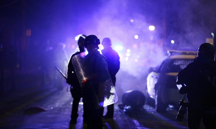 Police officers watch protesters as smoke fills the streets in Ferguson, Mo., on Nov. 25, 2014. In the wake of Michael Brown's death, the federal government wants to require the Ferguson Police Department to check all new hires against a database of police officers stripped of their law enforcement licenses for misconduct. The database contains the names of about 20,000 former officers who have been pushed out of law enforcement. Since it's been used inconsistently, many officers who are stripped of their badges in one jurisdiction are free to move to another. (AP Photo/Charlie Riedel)