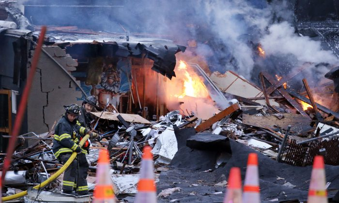 Firefighters move a hose into position as flames burn in the rubble left from an early morning explosion Wednesday, March 9, 2016, in Seattle. The explosion heavily damaged buildings and injured multiple firefighters. (AP Photo/Elaine Thompson)