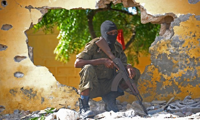 A Somali soldier stands guard next to the site where al-Shabab militants carried out a suicide attack against a military intelligence base in Mogadishu on June 21, 2015. (Mohamed Abdiwahab/AFP/Getty Images)