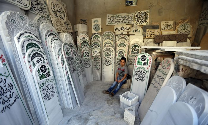 A Syrian boy sits at a tombstone shop at the entrance of a cemetery in Damascus on Sept. 23, 2015. (Joseph Eid/AFP/Getty Images)