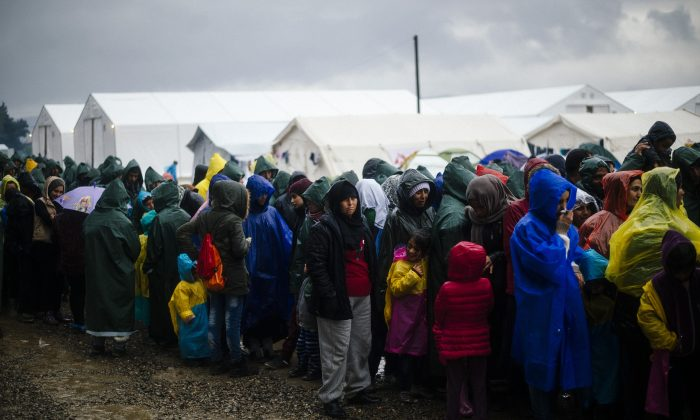 People queue in the rain for soup on March 9, 2016, in a makeshift camp at the Greek-Macedonian border, near the Greek village of Idomeni, where thousands of refugees and migrants are stranded by the Balkan border blockade. (Dimitar Dilkoff/AFP/Getty Images)