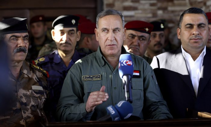 "Iraqi Defense Minister Khaled al-Obeidi (C) speaks to reporters at a military a base outside Tikrit, 80 miles north of Baghdad, Iraq, on March 9, 2016. Al-Obeidi played down fears of the Islamic State's chemical weapons capabilities, saying the group lacks ""chemical capabilities."" The attacks the group has carried were only intended to ""hurt the morale of our fighters,"" as they have so far not caused any casualties he said. (AP Photo/Hadi Mizban)"
