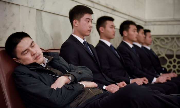 A man sleeps next to civilian guards inside the Great Hall of the People before the Second Plenary Meeting on March 9, 2016 in Beijing, China. The 12th National People's Congress goes on till March 16th. (Etienne Oliveau/Getty Images)