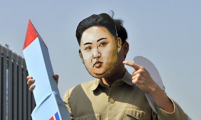 A South Korean activist wearing a mask of North Korean leader Kim Jong-Un holds a mock missile during a rally denouncing North Korea's rocket launch and the three-generational dictatorship, in Seoul on April 15, 2012. (JUNG YEON-JE/AFP/Getty Images)