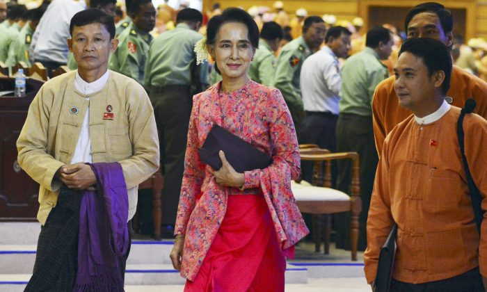 FILE - In this Feb. 1, 2016 file photo, Myanmar opposition leader Aung San Suu Kyi, center, walks along with other lawmakers of her National League for Democracy party as they leave after a regular session of the lower house of parliament in Naypyitaw, Myanmar. Nobel laureate Suu Kyi's decades-long battle to bring democracy to Myanmar is likely to come to fruition on Thursday, March 10 with a whimper, not a bang. Despite leading her NLDP to a smashing election victory, Suu Kyi seems certain not to become her country's leader. Suu Kyi, 70, cannot be president because the constitution bars anyone with a foreign spouse or children from holding the executive office. Suu Kyi's two sons are British, as was her late husband. (AP Photo/Aung Shine Oo, File)