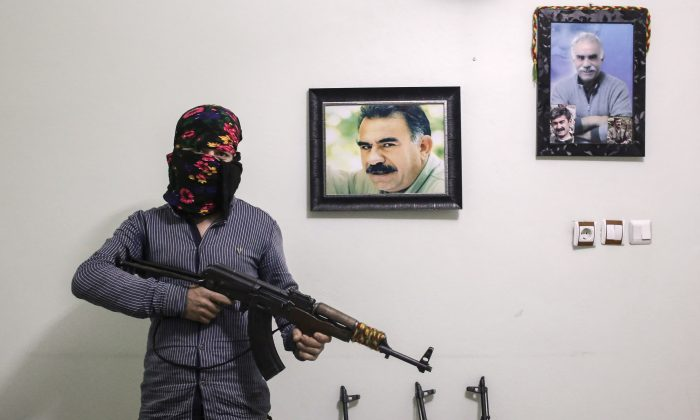 A member of a armed group Patriotic Revolutionary Youth Movement (YDG-H), a youth division of the Kurdistan Workers' Party (PKK), with his AK-47 next to a pictures of the jailed Kurdish rebel leader Abdullah Ocalan in a house in southeastern Turkish city of Nusaybin, Turkey, on Feb. 25, 2016. Since mid-December, the Turkish security forces placed to several predominantly Kurdish cities in Turkey under 24-hour martial law and curfew on the premise of restoring public order. (Cagdas Erdogan/Getty Images)