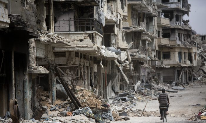 A man rides a bicycle through a devastated part of Homs, Syria, on June 5, 2014. (AP Photo/Dusan Vranic)