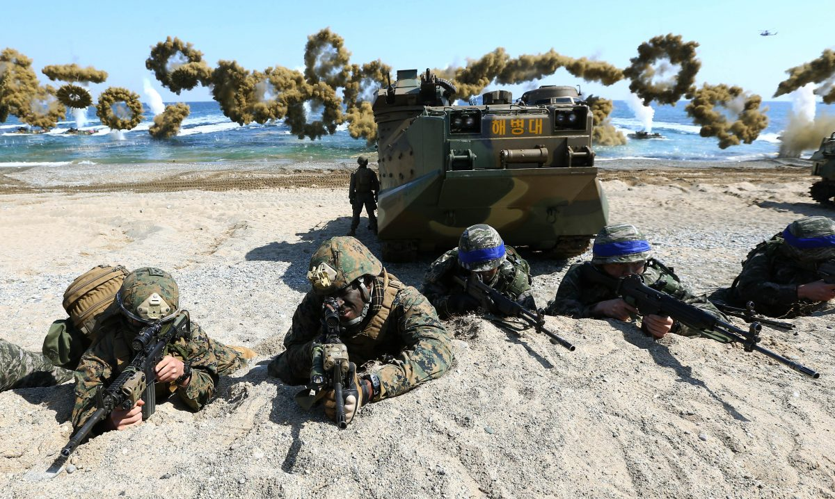 "U.S. Marines (L) and South Korean Marines, wearing blue headbands on their helmets, take positions after landing on the beach during the joint military combined amphibious exercise, called Ssangyong, part of the Key Resolve and Foal Eagle military exercises, in Pohang, South Korea, on March 12, 2016. North Korea said Saturday its military is ready to pre-emptively attack and ""liberate"" the South in its latest outburst against the annual joint military drills by the United States and South Korea. (Kim Jun-bum/Yonhap via AP)"