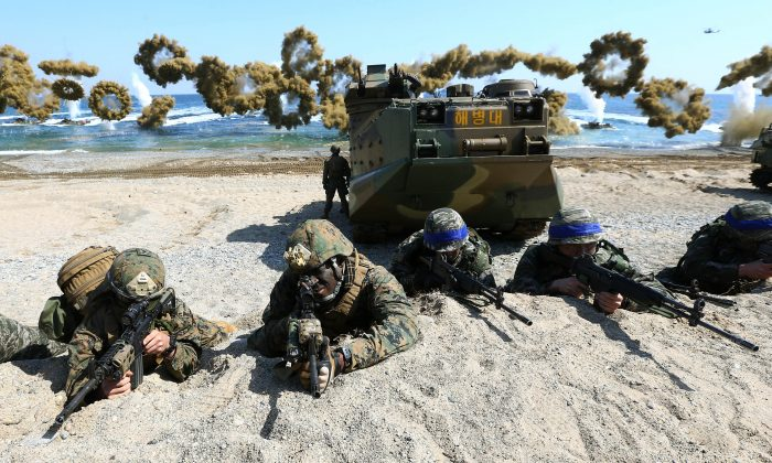 U.S. Marines (L) and South Korean Marines, wearing blue headbands on their helmets, take positions after landing on the beach during the joint military combined amphibious exercise, called Ssangyong, part of the Key Resolve and Foal Eagle military exercises, in Pohang, South Korea, on March 12, 2016. (Kim Jun-bum/Yonhap via AP)