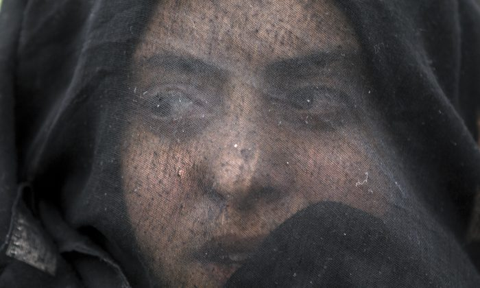 A woman shouts slogans during a protest by migrants demanding the opening of the border between Greece and Macedonia at the northern Greek border station of Idomeni, on March 12, 2016. Up to 14,000 people are stranded on the outskirts of the village of Idomeni in a makeshift camp. (AP Photo/Vadim Ghirda)