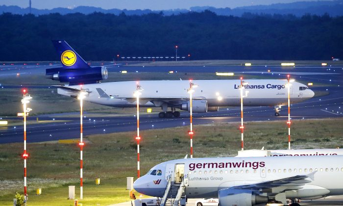 A cargo aircraft, top, with remains of several people who died in the Germanwings plane crash in France lands at the airport in Dusseldorf, Germany, Tuesday, June 9, 2015. 150 people died in the plane crash on March 24. (AP Photo/Michael Probst)