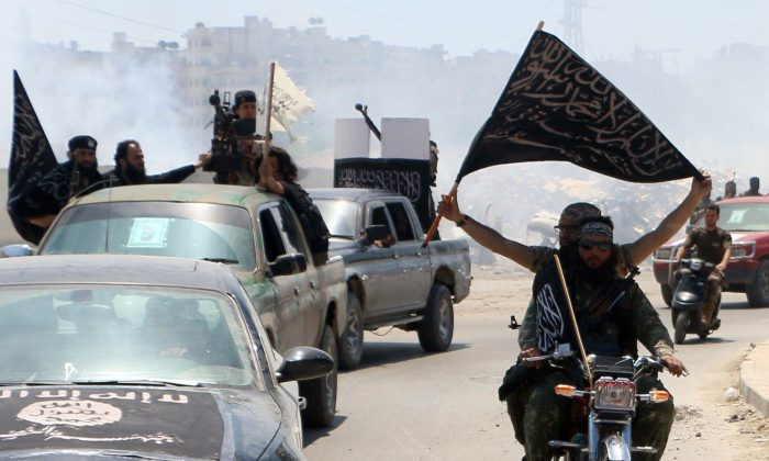 Fighters from Al-Qaida's Syrian affiliate Al-Nusra Front drive in the northern Syrian city of Aleppo flying Islamist flags as they head to a frontline, on May 26, 2015. (Fadi al-Halabi/AFP/Getty Images)