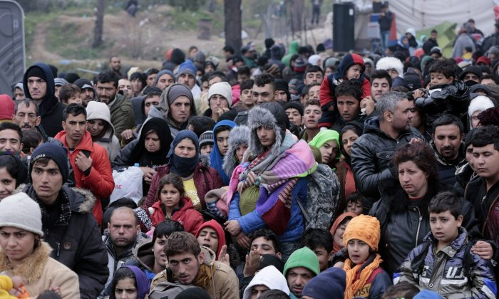 Refugees wait to pass through a Greek police cordon before crossing the Greek-Macedonian border, near the village of Idomeni, Greece, on Dec. 4, 2015. (Milos Bicanski/Getty Images)