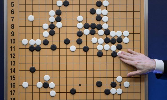 A commentator in a media room positions pieces forming a replica of a game between 'Go' player Lee Se-Dol and a Google-developed super-computer, in Seoul on March 13, 2016. (ED JONES/AFP/Getty Images)