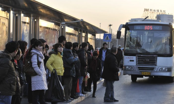 Passengers wait to board a bus at a stop in Beijing on February 1, 2010.   (OLLI GEIBEL/AFP/Getty Images)