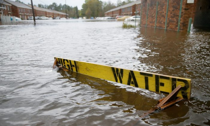 """Flood waters partially submerge a """"HIGH WATER"""" sign on Rufus Bankston Road west of Hammond, La., on March 11, 2016. (David Grunfeld/NOLA.com The Times-Picayune via AP)"""