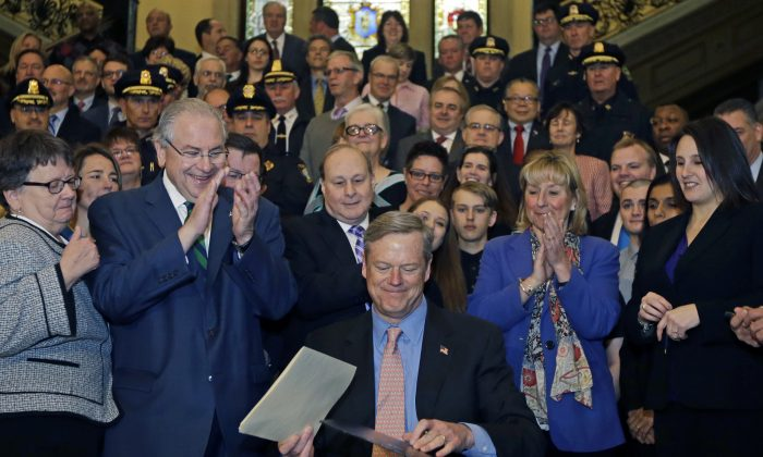 Massachusetts Gov. Charlie Baker smiles after signing sweeping legislation aimed at reversing a deadly opioid addiction crisis, during a signing ceremony at the Statehouse, Monday, March 14, 2016, in Boston. Applauding behind, left, is House Speaker Robert DeLeo, along with Senate President Stanley Rosenberg, directly behind, and members of the legislature, law enforcement, health care providers, community leaders and individuals in recovery. (AP Photo/Elise Amendola)