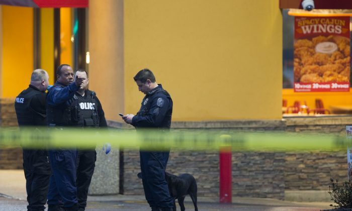 Police stand outside a Popeyes restaurant during an investigation into the shooting of a Prince George's County police officer outside a police station, on Sunday, March 13, 2016, in Hyattsville, Md. (AP Photo/Evan Vucci)