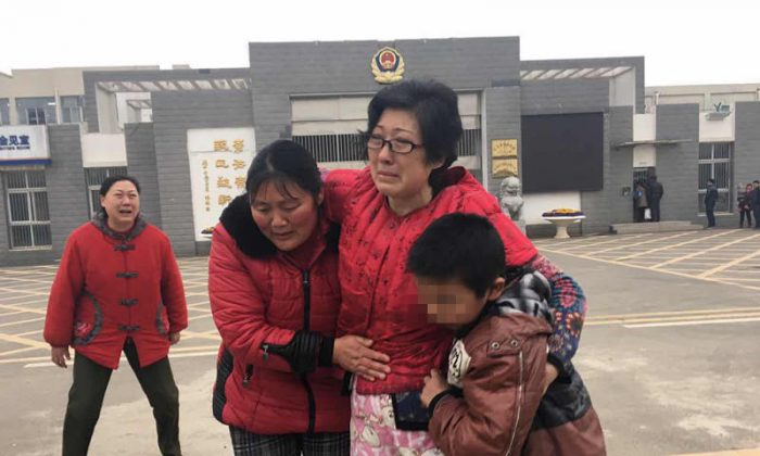 Li Zhengqin (center) carries by her adopted son and his biological mother after leaving the Changzhou's Women's Prison. (Beijing Times)