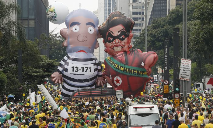 """Demonstrators parade large inflatable dolls depicting Brazil's former President Luiz Inacio """"Lula"""" da Silva in prison garb and current President Dilma Rousseff dressed as a thief, with a presidential sash that reads """"Impeachment,"""" in Sao Paulo, Brazil, on March 13, 2016. The corruption scandal at the state-run oil giant Petrobras has ensnared key figures from Rousseff's Workers' Party, including her predecessor and mentor, Lula da Silva, as well as members of opposition parties. (AP Photo/Andre Penner)"""