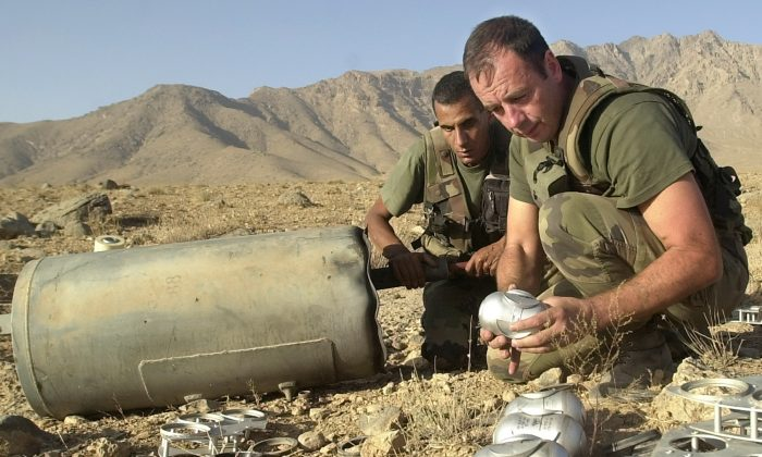 Soldiers with the French contingent of the International Security Assistance Force (ISAF) unload Russian made cluster bombs from a container found about 18 miles north of Kabul, Afghanistan, on Oct. 9, 2002. (AP Photo/Lynne Sladky)