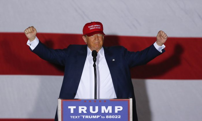 Republican presidential candidate Donald Trump raises his arms during a campaign rally in Boca Raton, Fla., Sunday, March 13, 2016. (AP Photo/Paul Sancya)