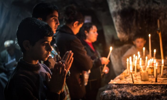 Iraqi Christians light candles inside a shrine on the grounds of Mazar Mar Eillia (Mar Elia) Catholic Church, that has now become home to hundreds of them, forced to flee their homes due to the Islamic State advances, in Erbil, Iraq, on Dec. 12, 2014. (Matt Cardy/Getty Images)