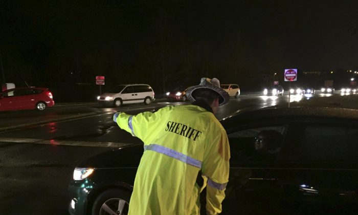In this photo provided by ABC11, an Alamance County Sheriff Dept. officer directs traffic near exit 154 on Interstate 40 after multiple vehicle accidents Sunday, March 13, 2016, in central North Carolina. Authorities say dozens of vehicles were involved in a series of wrecks that injured over a dozen people and temporarily shut down part of Interstate 40. (Tim Pulliam/ABC11 via AP) MANDATORY CREDIT