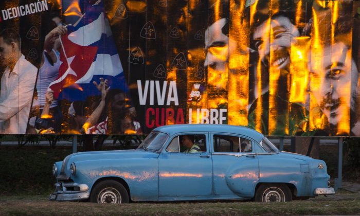 """A taxi driving a classic American car passes a billboard that reads in Spanish: """"Long live free Cuba"""" in Havana, Cuba, Monday, March 14, 2016. U.S. President Barack Obama will travel to Cuba on March 20. The trip will mark a watershed moment in U.S.-Cuba relations, making Obama the first sitting U.S. president to set foot on the island in nearly seven decades. (AP Photo/Desmond Boylan)"""
